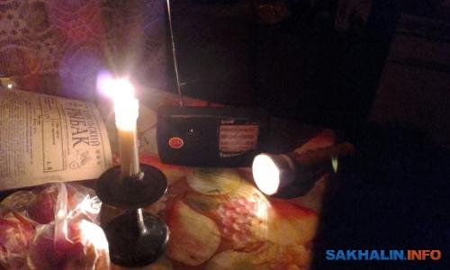 Жители Северо-Курильска проводят вечер подзвуки радиоприемника ипри свечах