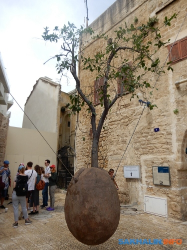 """Апельсиновое дерево, парящее надземлей, символ Яффо. Поодной изверсий, оноолицетворяет народ Израиля, который будет творить и""""плодоносить"""" даже вотрыве отсвоей земли, чтона самом деле ипроисходило (и происходит) сотни лет"""