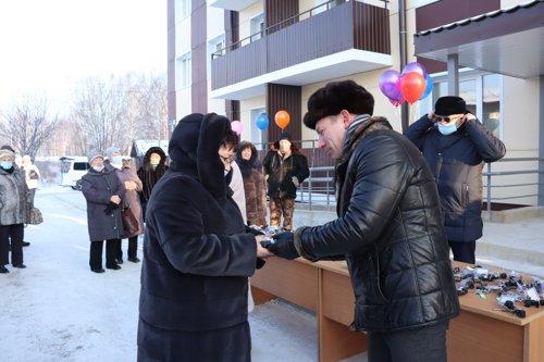 Мэр Егор Белобаба вручает ключи переселенцам, видны незастекленные балконы, фото мэрии