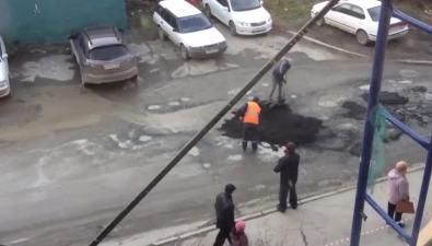 Рабочие кидают асфальт влужу возле дома №105 поулице Украинской вЮжно-Сахалинске